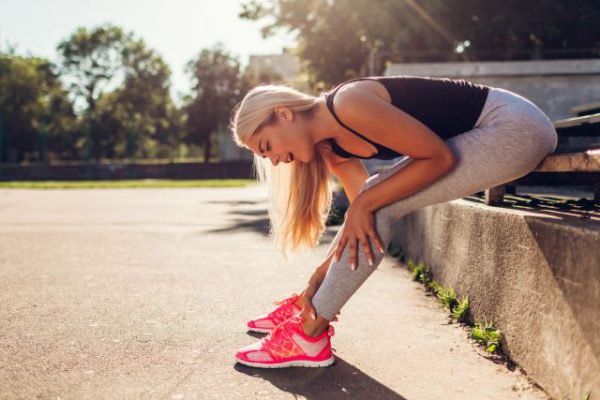 Young woman athlete touching her ankle after running on sportsground in summer. Injury during training